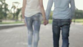 Un uomo e una donna prendono ogni altre le mani e si allontanano archivi video