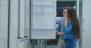 Un uomo e una donna scegliere un frigorifero per comprare in una nuova casa stock footage