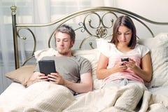 Un uomo e una donna si trovano a letto e leggono i libri elettronici Fotografia Stock Libera da Diritti