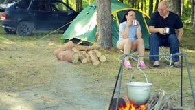 Un uomo e una donna stanno sedendo dalla tenda, tè bevente e stanno guardando il vaso appendere sopra il fuoco archivi video