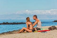 Un uomo e una donna stanno sedendo sulla spiaggia sabbiosa Fotografia Stock