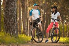 Un uomo e una donna vada ciclare nel legno Bici alla natura fotografie stock libere da diritti