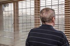 Un uomo e una finestra bagnata Fotografie Stock Libere da Diritti