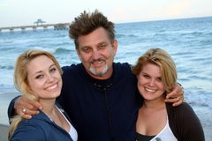 Un uomo ed adolescenti sulla spiaggia Fotografia Stock