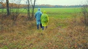 Un uomo ed agronomi di una donna in un impermeabile che camminano su un campo arato stock footage