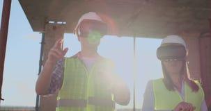 Un uomo ed ingegneri di una donna ad un cantiere in vetri di VR dirigere la costruzione di un edificio che discutono a stock footage