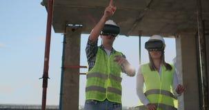 Un uomo ed ingegneri di una donna ad un cantiere in vetri di VR dirigere la costruzione di un edificio che discutono a video d archivio