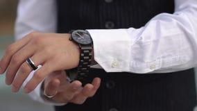Un uomo elegante in una serie classica mette un orologio sulla sua mano Uomo d'affari con un orologio del progettista sulla sua m video d archivio