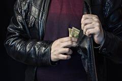 Un uomo elimina i soldi da un taschino da giacca, un fondo nero, un rivestimento nero fotografia stock