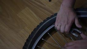 Un uomo elimina una macchina fotografica da una ruota di bicicletta stock footage