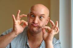 Un uomo emozionale con le espressioni facciali differenti dei baffi sul fronte immagine stock libera da diritti