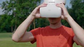 Un uomo entra nella struttura, mette sopra la sua testa una cuffia avricolare di VR nel parco e guarda intorno