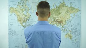 Un uomo esamina una mappa del mondo archivi video