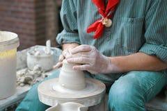 Un uomo fa un lanciatore di argilla fotografia stock