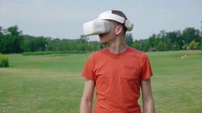 Un uomo facendo uso di una cuffia avricolare di VR al parco ed ai giri la sua testa alla destra