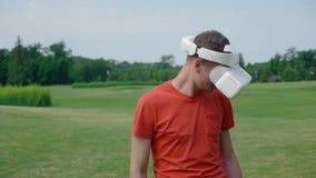 Un uomo facendo uso di una cuffia avricolare di VR al parco ed ai giri la sua testa giù