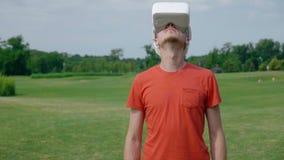 Un uomo facendo uso di una cuffia avricolare di VR nel parco e gira il suo si dirige