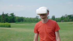 Un uomo facendo uso di una cuffia avricolare di VR nel parco, evitante gli ostacoli e guardante intorno