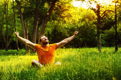 Un uomo felice sta sedendosi sull'erba verde ed alzandosi arma fino al cielo Fotografie Stock