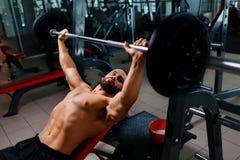 Un uomo forte che risolve gli esercizi con un bilanciere su un fondo della palestra Un tipo atletico tiene il piatto del bilancie immagini stock