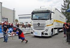 Un uomo forte tira un grande camion Immagini Stock Libere da Diritti