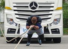 Un uomo forte tira un grande camion Fotografia Stock