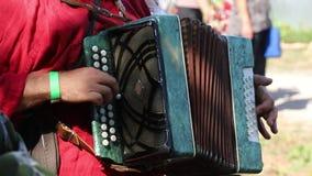Un uomo in gente russe costumes la fisarmonica dei giochi in natura stock footage