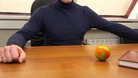 Un uomo gioca con una piccola palla su una scrivania stock footage