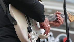 Un uomo gioca sulle corde della chitarra elettrica con un corpo bianco Movimento lento stock footage