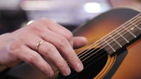 Un uomo gioca una chitarra acustica Primo piano della mano che colpisce le serie della chitarra archivi video