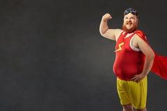 Un uomo grasso divertente in un costume del supereroe Immagini Stock