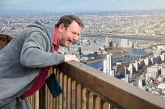 Un uomo grida nel timore che esamina il panorama di grande città da sopra immagine stock libera da diritti