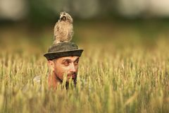 Un uomo guarda dall'erba con un gufo sulla sua testa e guarda nelle direzioni differenti fotografia stock