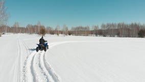 Un uomo guida un quadrato sopra un campo dell'inverno nella foresta video d archivio