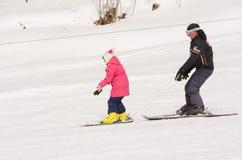 Un uomo impara sciare adolescente su una stazione sciistica innevata Dombai del pendio Fotografia Stock Libera da Diritti