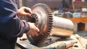 Un uomo inserisce un cuscinetto in un grande ingranaggio del metallo - concetto dell'industria video d archivio