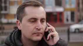 Un uomo interessato alla conversazione sul telefono all'aperto all'autunno video d archivio
