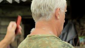 Un uomo invecchiato mezzo si è vestito in una maglietta cachi, radentesi dalla donna con un tagliatore camicia cachi L'uomo senio stock footage