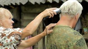 Un uomo invecchiato mezzo si è vestito in una maglietta cachi, radentesi dalla donna con un tagliatore camicia cachi L'uomo senio video d archivio
