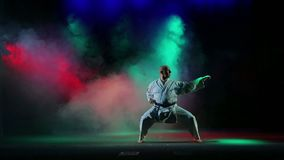 Un uomo in kimano bianco è impegnato nel karatè stock footage