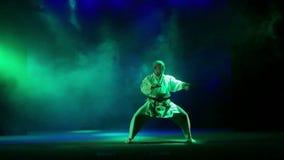 Un uomo in un kimano bianco è impegnato nel karatè - esegue la regione selvaggia sui precedenti di fumo colorato archivi video