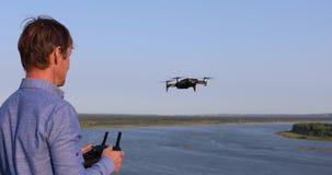 Un uomo lancia il quadcopter Fuco volante sopra il fiume e la foresta un giorno soleggiato archivi video