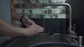 Un uomo lava una spatola con una spugna per lavare nella cucina video d archivio