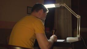 Un uomo lavora ad una tavola nello scuro Un uomo scrive a mano con una matita su carta Il piano generale dalla parte posteriore stock footage