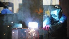 Un uomo lavora con un bruciatore - salda un angolo di metallo video d archivio