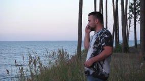 Un uomo lavora fuori orario sul telefono a fine settimana in un bello fondo del paesaggio video d archivio