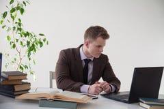 Un uomo lavora nell'ufficio all'impiegato di affari di computer immagini stock libere da diritti