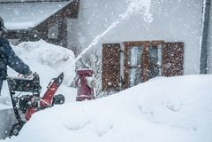 Un uomo libera la neve dai marciapiedi con lo sgombraneve a turbina in Baviera Germania fotografia stock libera da diritti