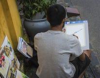 Un uomo locale che fa arte, a partire dalla vita reale, nella città antica del ` s di Hoi An Immagine Stock