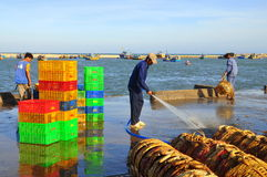Un uomo locale sta pulendo i suoi canestri che sono stati usati per il trasporto dei pesci dalla barca al camion Immagini Stock